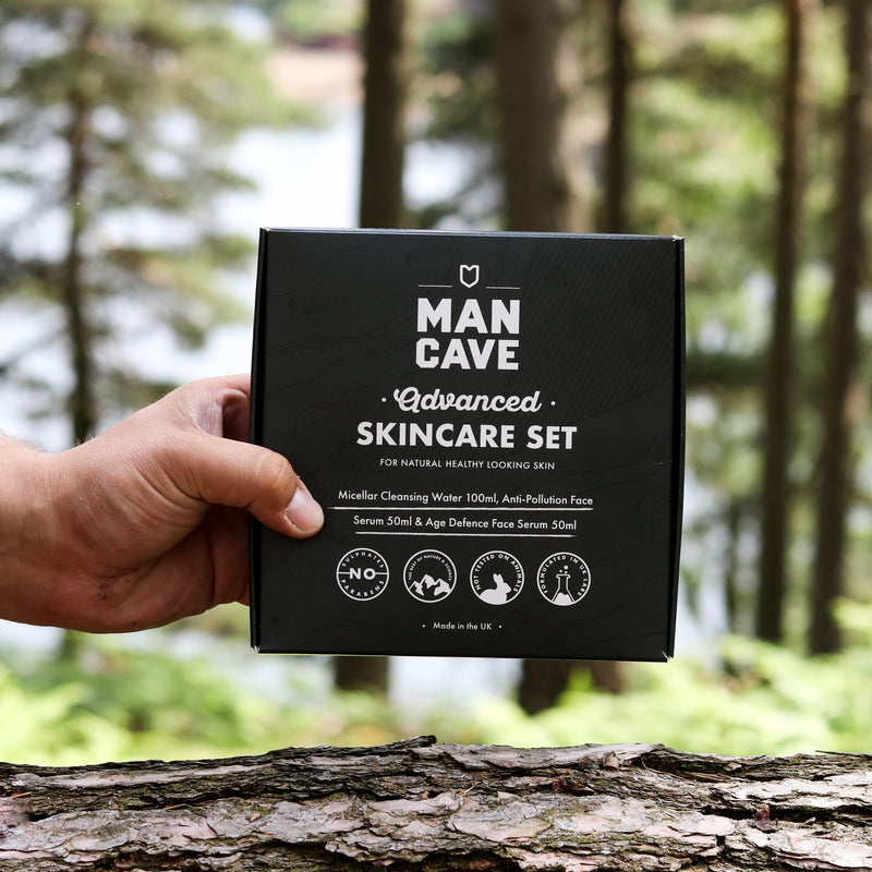 The black front cover of ManCave's Advanced Skincare Gift Set, containing the award winning ManCave Micellar Cleansing Water, ManCave Anti Pollution Face serum and ManCave Age Defence Serum. The gift set appears on a wooden log with greenery and a forest in the background.