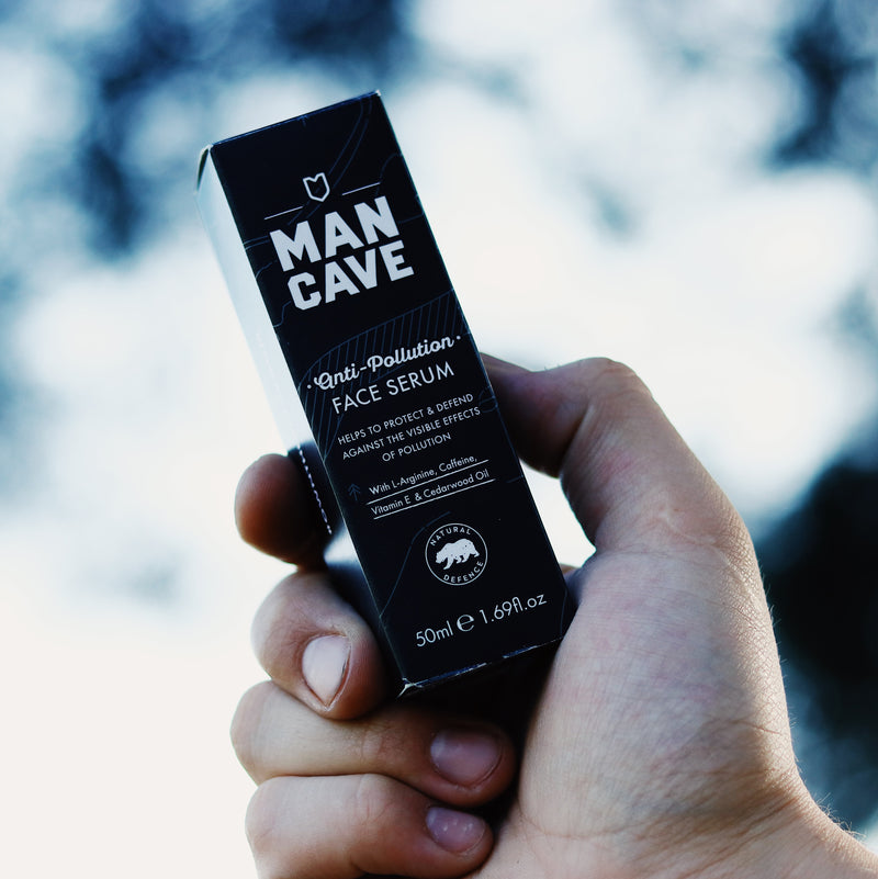 The ManCave anti Pollution face serum 50ml box being held by a mans hand in front of a blue sky and trees blurred in the background