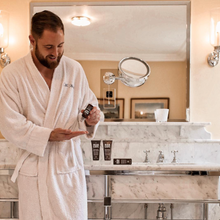A bearded man in a bath robe is applying the mancave blackspice beard oil to his palm with a marble bathroom and mirror in the background