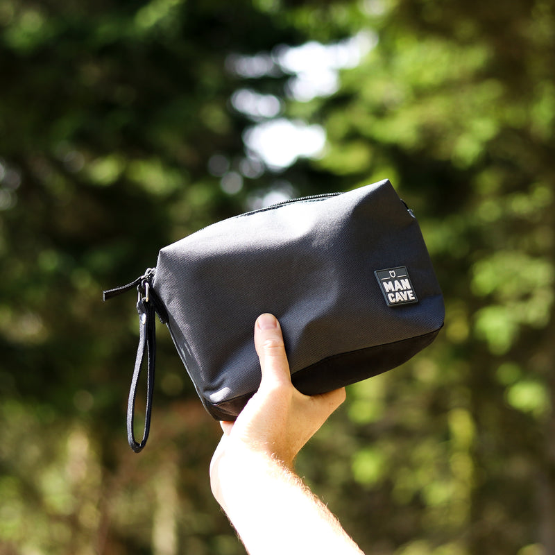 ManCave dark grey trial wash bag being held up by a mans hand with green trees in the background