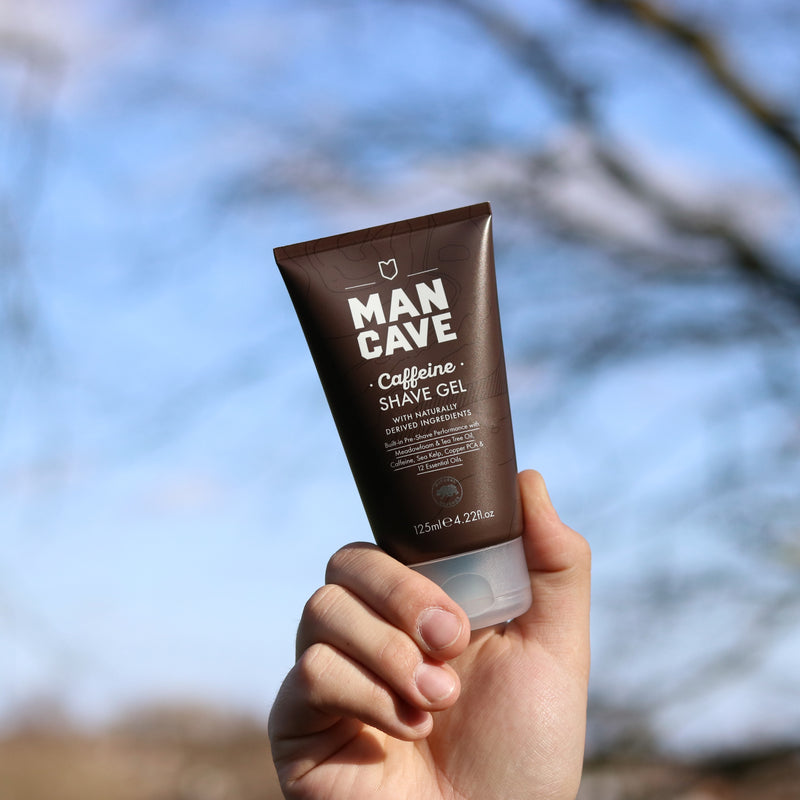 ManCave caffeine shave gel 125ml in a 100% recyclable brown tube being held up by a mans hadn't with trees and a blue sky in the background