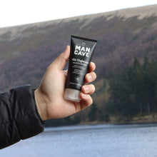 ManCave oil defence moisturiser 100ml in a 100% recyclable black tube being held by a mans hand with water and a lavender hillside in the background