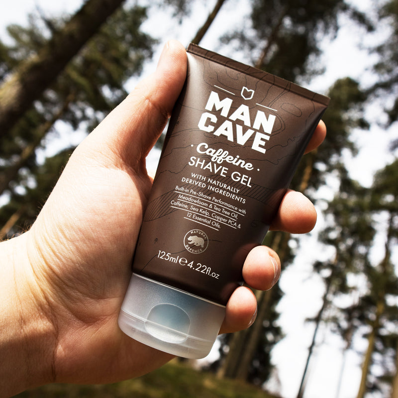ManCave caffeine shave gel 125ml in a 100% recyclable brown tube being held by a mans hand in front of a forest and blue sky