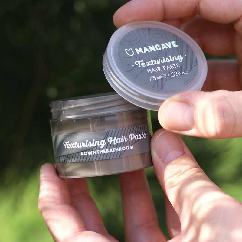 ManCave texturising hair paste grey tub being held in a mans hand with greenery in the background