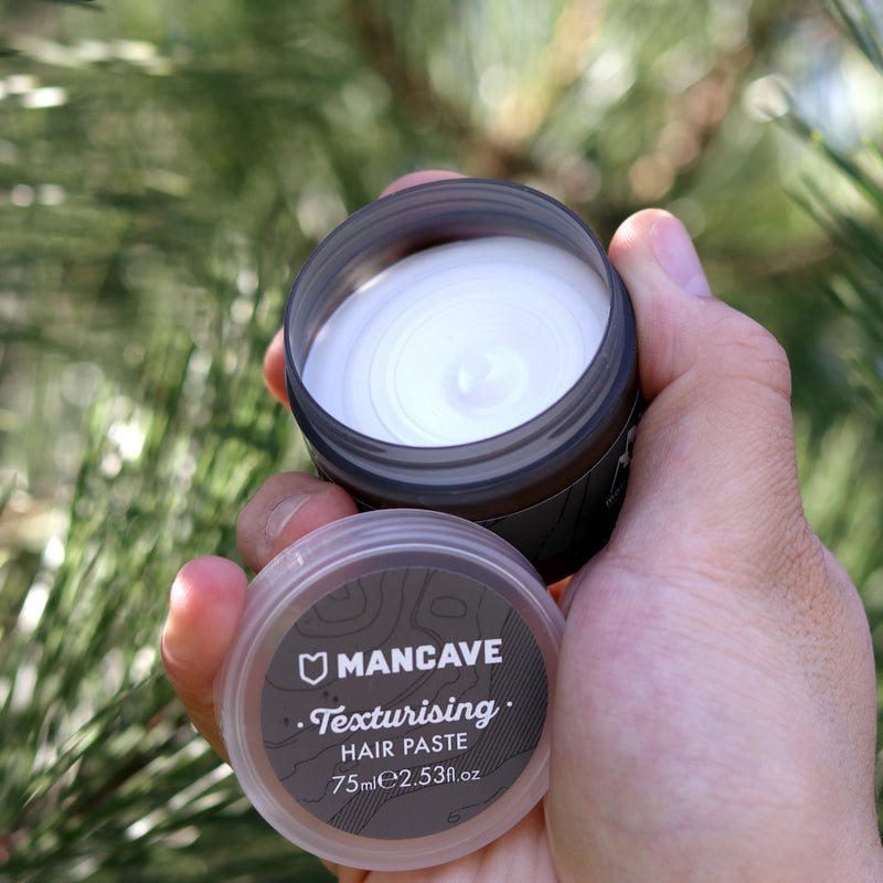 ManCave texturising hair paste 75ml in a grey tub being held by a mans hand with a tree in the background