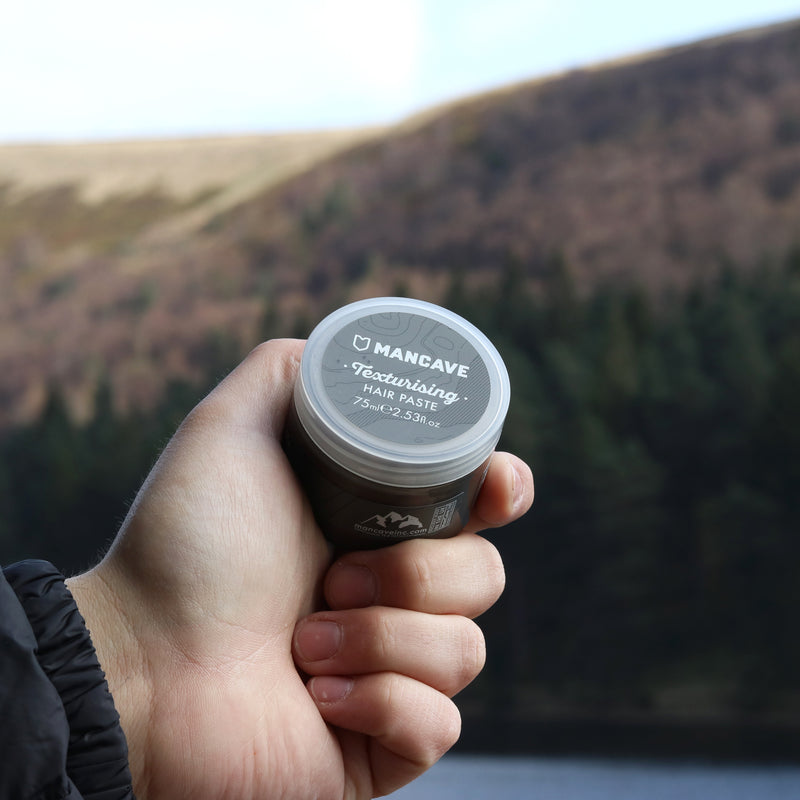 ManCave texturising hair paste 75ml in a grey tub being held by a mans hand in front of water and a lavender hillside