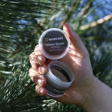 ManCave water based hair pomade is a clear gel in a grey tub being held by a mans hand with a tree in the background