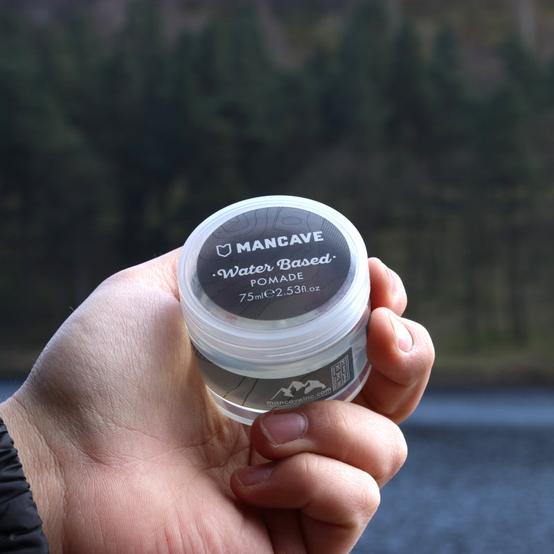 ManCave water based hair pomade in a clear and grey tub being held by a mans hand in front of water and trees blurred in the background