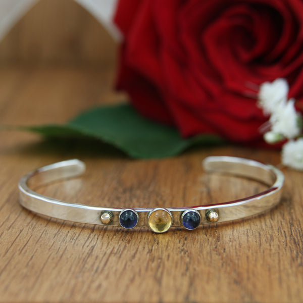 citrine iolite cabochon sterling silver cuff with 14 karat yellow gold accent rose background