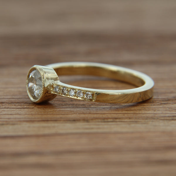 14k yellow gold milligrain texture .64cttw cener diamond .49ct I1 J/K internal characteristics crackle diamond band has rbc diamonds matching center 10=.15cttw bead set with milligrain detail