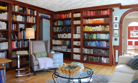 books arranged by color on bookshelves in a library
