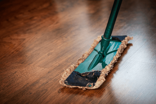 Cleaning wooden floors with a turquoise duster