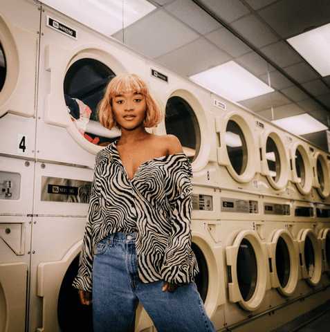 Girl standing in front of college dorm washing machines