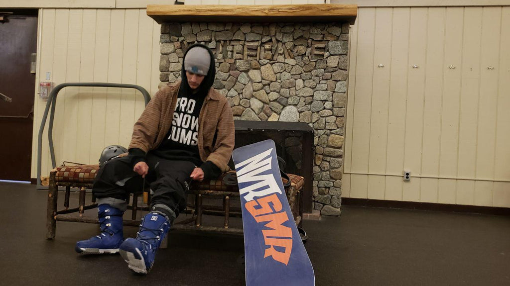 Pro Snow Bums Rider Pat Bixler with snowboard putting on snowboarding gear.