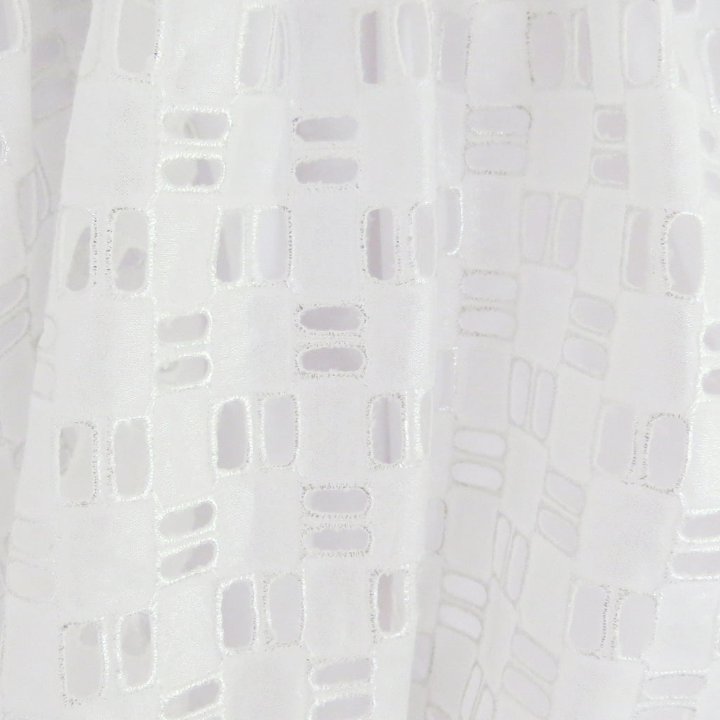 Summer silver foil cotton geometric broderie anglaise fabric close up.