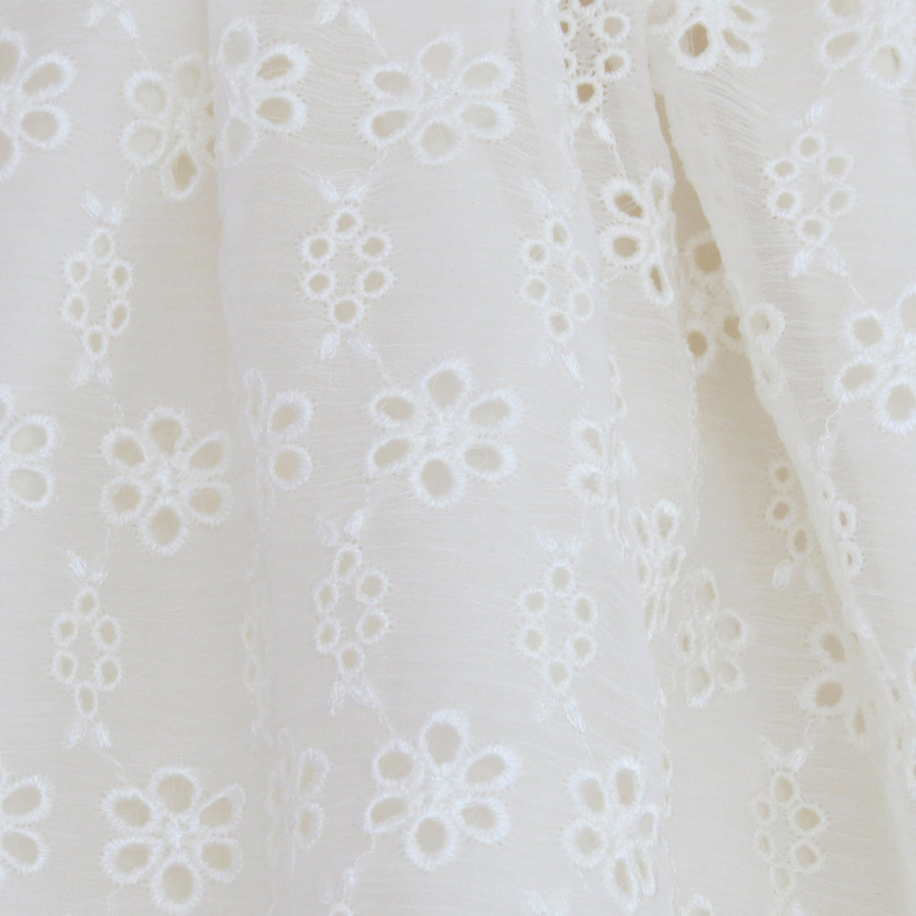 Summer Childs cream silk broderie anglaise dress fabric close up.