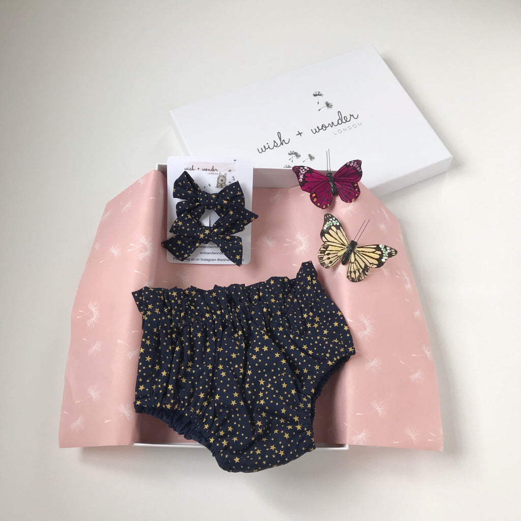 Baby and Toddler high waisted bloomer shorts and matching hair bow set in gold star print on midnight blue ground.