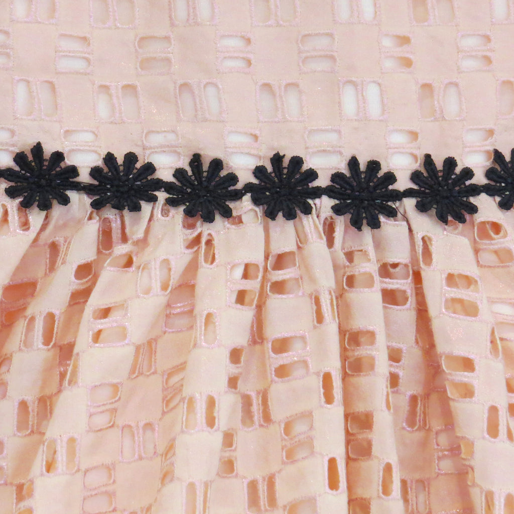 Childs Summer peach cotton geometric broderie anglaise dress with black daisy trim, rose gold foil fabric close up.