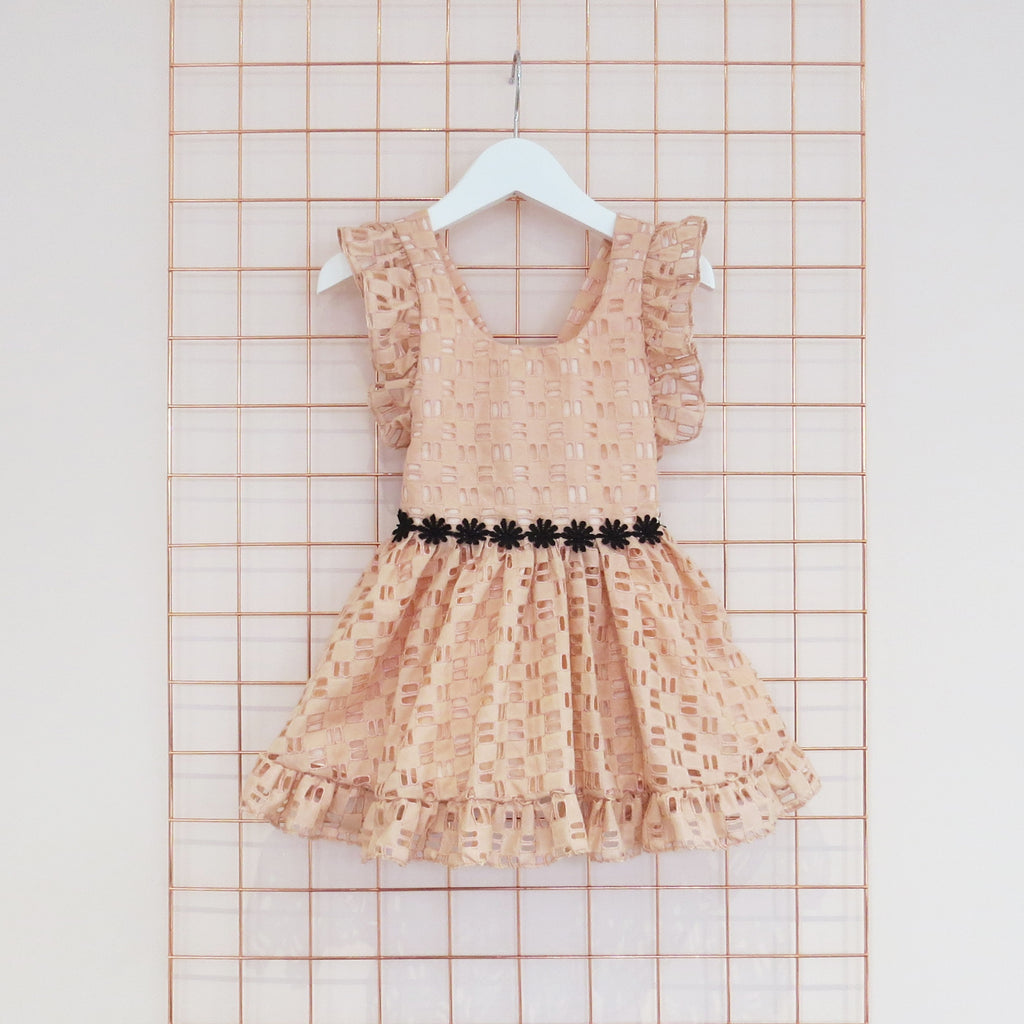 Childs Summer peach cotton geometric broderie anglaise dress with black daisy trim, rose gold foil and frill sleeves.