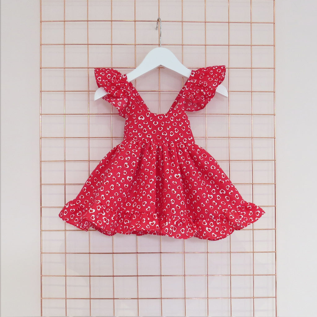 Childs Summer red conversational heart print dress in bright red and white with frill sleeves.