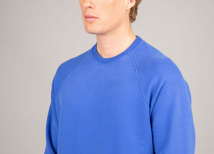 Close up of chest on mens royal blue organic cotton sweatshirt by Finisterre