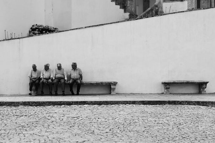 Grayscale photo of four men sitting on bench in the street - W-Photographie