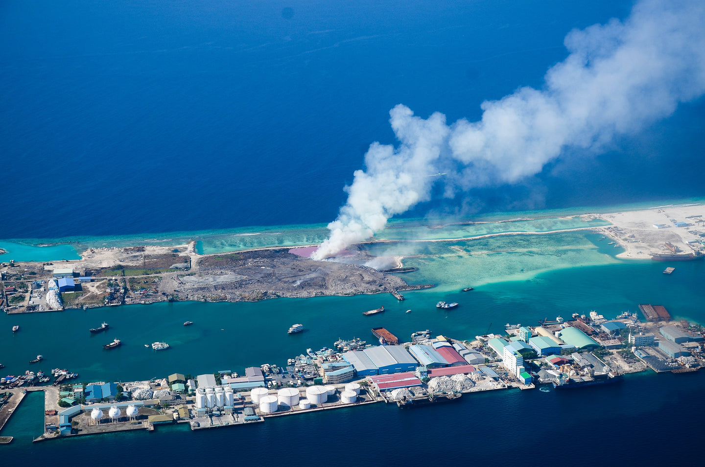 Aerial view of land blowing smoke - W-Photographie