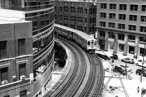 Grayscale photography of train railroad near building - W-Photographie