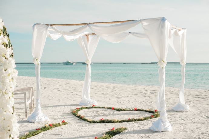 White fabric canopy with green heart floor decor at beach - W-Photographie