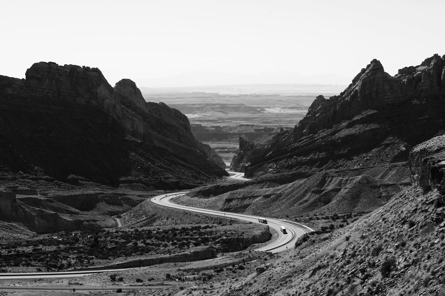 Grayscale photo of roadway surrounded with rocky mountains - W-Photographie
