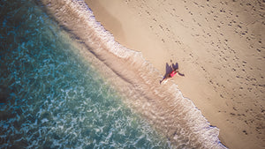 Photo of person lying beside seashore - W-Photographie