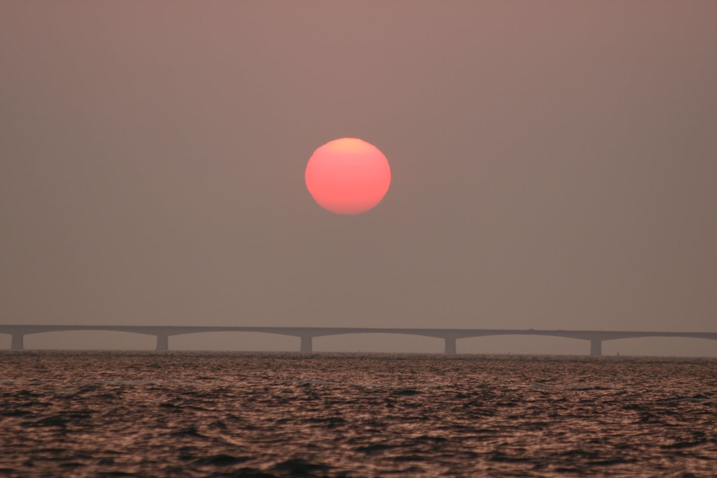 Sunset over bridge near body of water