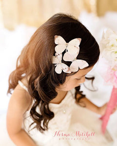 Bridesmaid wears cream and white butterfly hair clips