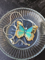 Turquoise  blue butterfly on a glass dish
