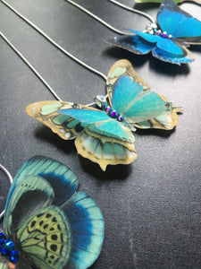 Close detail of bright silk butterfly necklaces by Flutter Designs