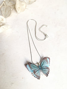 Pale blue silk butterfly necklace on a sterling silver snake chain