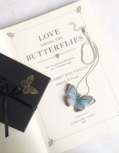 Vintage book displays a maple blue butterfly necklace