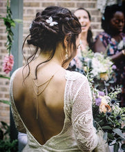 A bride in a backless dress wears silk butterfly hair pins in her braided hair