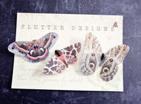 Three silk moth hair clips by Flutter Designs in shades of red and brown