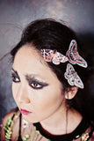 A gothic styled model wears three silk moth hair clips with Swarovski Crystals