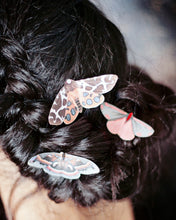A model with black hair wears silk moth hair clips by Flutter Designs