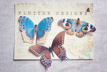 Three handmade blue silk butterfly hair clips on a gift card