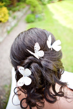 A dark haired bride wears silk butterfly hair pins in her loosely tied braided hair