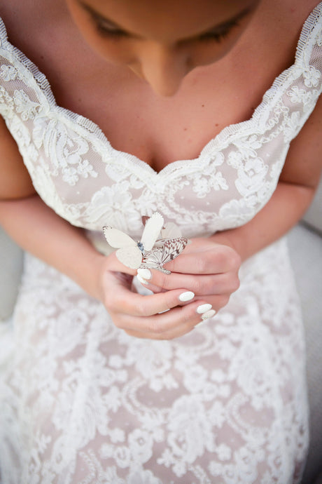 A bride holds a set of delicate little silk butterfly hair pins