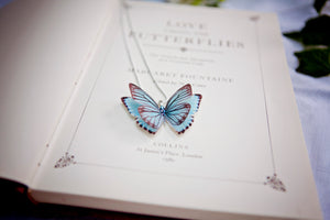 Something blue butterfly necklace rests on a vintage book