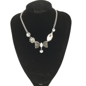 JEWELRY, - SILVER NECKLACE WITH CLEAR CRYSTAL ACCENTS AND BOW TIE CENTER.