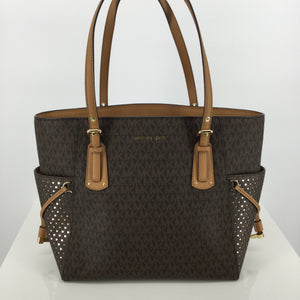 ACCESSORIES,PURSES AND HANDBAGS - SHINE LIKE A STAR WITH THIS CLASSIC BROWN MK MONOGRAM TOTE! LIKE NEW CONDITION ON INSIDE AND OUT! HAS STAR CUT-OUTS ON BOTH SIDE POCKETS REVEALING GOLD UNDERNEATH. THE INSIDE HAS 9 SLOT POCKETS, 1 ZIPPER POCKET, AND 1 DIVIDING POCKET WITH ZIPPER CLOSURE.