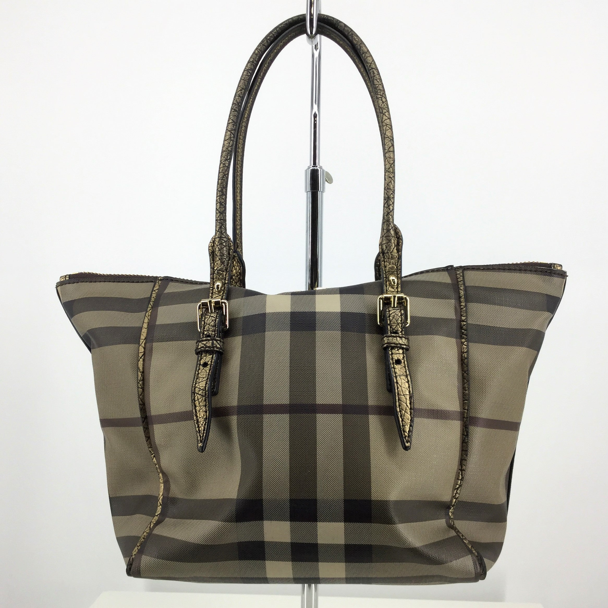 BURBERRY HANDBAG - BEAUTIFUL COATED CANVAS BURBERRY TOTE WITH BRONZE DETAILING. GOLD HARDWARE. ONE LARGE ZIPPER POCKET INSIDE AND TWO SLIP POCKETS. SOME NORMAL WEAR AND TEAR, AND FADING ON HANDLES.