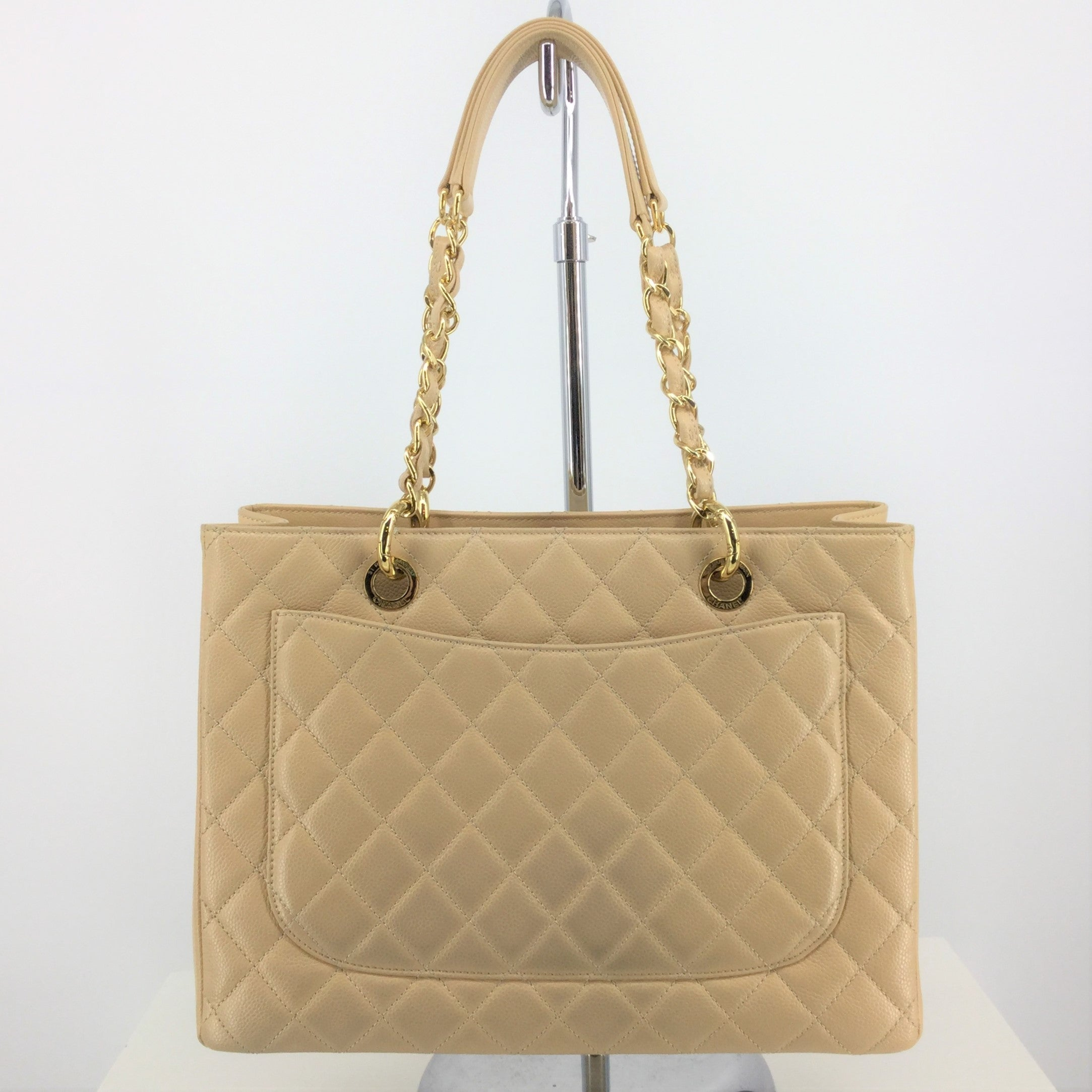 Chanel Grand Shopper Tote - BEAUTIFUL QUILTED BEIGE LEATHER CHANEL GRAND SHOPPER TOTE. COMES WITH DUST BAG AND AUTHENTICATION CARD. DOES HAVE COLOR TRANSFER ON BACK SIDE. OTHERWISE, IN AMAZING CONDITION. GOLD HARDWARE. ZIPPER DIVIDER POUCH.  ONE LARGE SLIP POCKET AND ONE LARGE ZIPPER POCKET INSIDE.