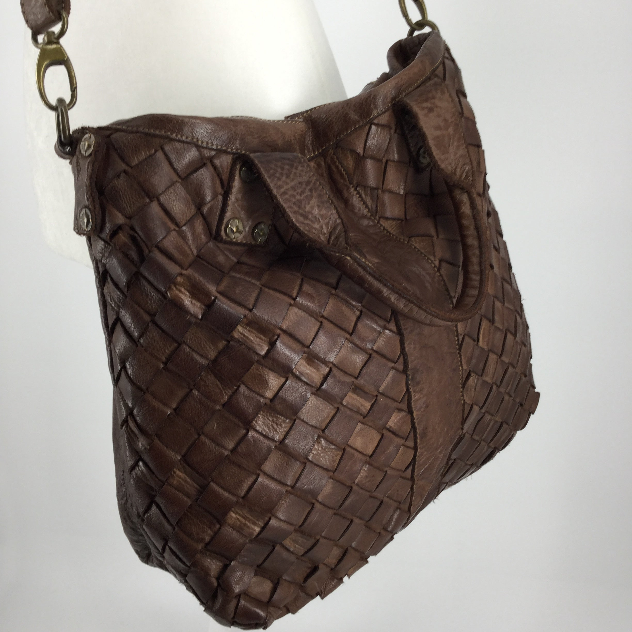 ACCESSORIES,PURSES AND HANDBAGS - THIS GEORGEOUS WOVEN LEATHER HANDBAG IS MADE IN ITALY WITH WONDERFUL CRAFTSMANSHIP. THE PEBBLED LEATHER IS SOFT AND SUPPLE, IN A RICH, WARM BROWN. THIS BAG HAS BOTH SHORT, CORDED HANDLES FOR ARM CARRY PLUS AN ADJUSTABLE CROSSBODY STRAP. IT IS VERY ROOMY INSIDE AND FEATURES 2 SMALLER SLIP POCKETS PLUS A LARGER ZIP POCKET. IT ZIPS ACROSS THE TOP TO SECURE YOUR BELONGINGS. MAKE THIS UNIQUE BAG YOURS TODAY!